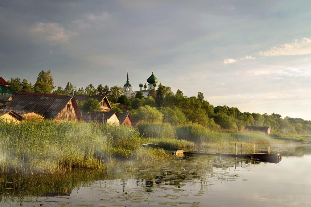 Вид на деревню и церковь у реки.