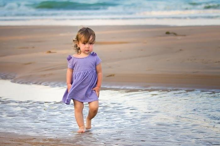 Маленькая девочка идет по пляжу