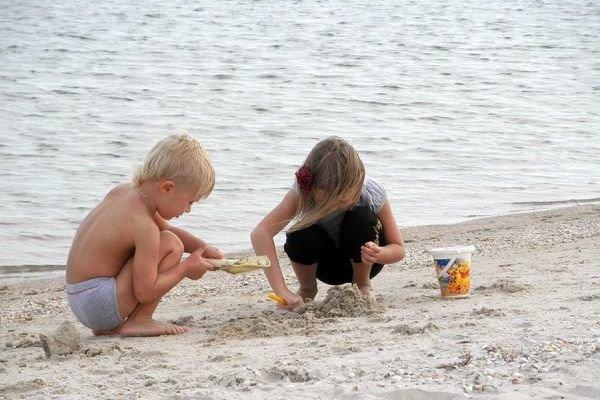 Дети играют в песке на пляже