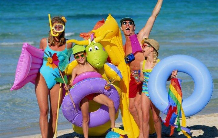 Семья с детьми на пляже с плавательными кругами